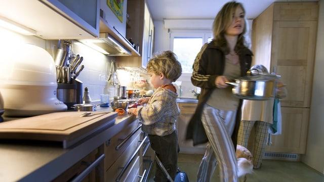 Mamma e figl vid cuschinar.