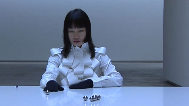 Frau sitzt an einem weissen Tisch, auf dem silberne Kugeln rollen