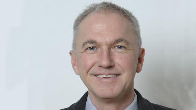 Jürg Wiedemann schaut in die Kamera und lächelt.