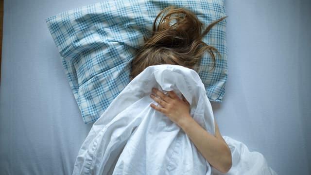 Ein Mädchen liegt in einem Bett, den Kopf zugedeckt mit der Bettdecke.