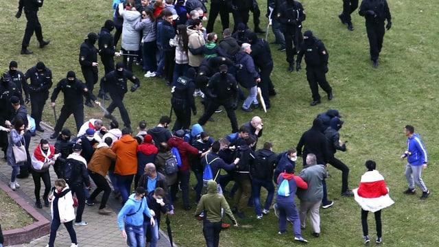 Uniformierte Polizisten prügeln auf Passanten ein.