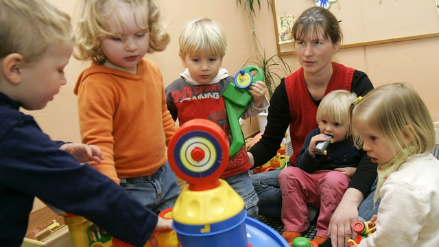 Eine Kinderbetreuerin sitzt mit einem Kind auf dem Schoss auf dem Boden. Vier weitere Kinder stehen drum rum und alle spielen zusammen.