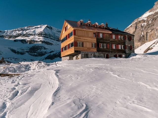 SAC-Hütte vor Bergen.
