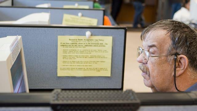 Symbolbild: Ein Mann blickt konzentriert in einen Bildschirm.