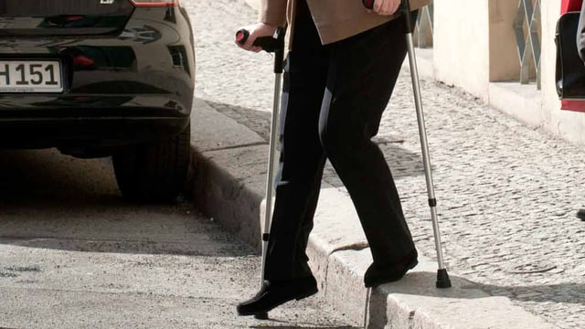 Eine Frau geht an Krücken.