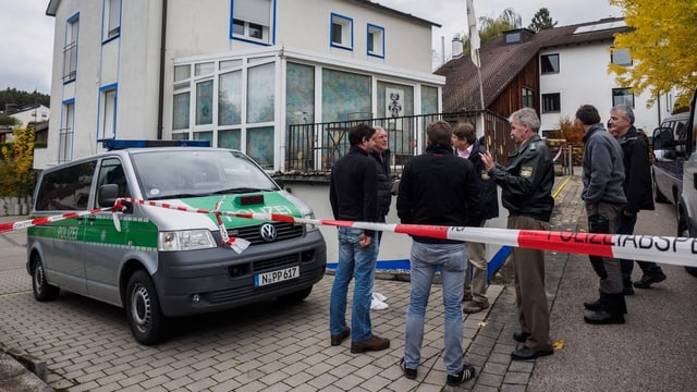 Polizeiabsperrung und -wagen vor Tatort.