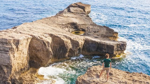 Ein Mann auf einem Felsen am Meer.