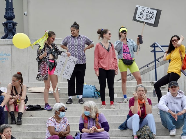 Frauen sitzen oder stehen mit Plakaten auf dem Theaterplatz.