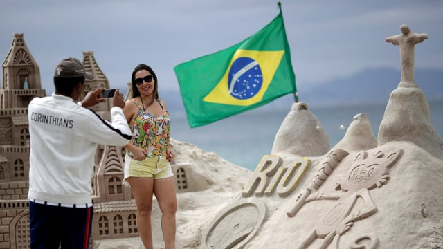 Auf einer Sandburg weht eine brasilianische Flagge.