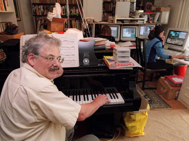 Ein Mann mit Hemd am Klavier, im Hintergrund Frauen an Computern sitzend.