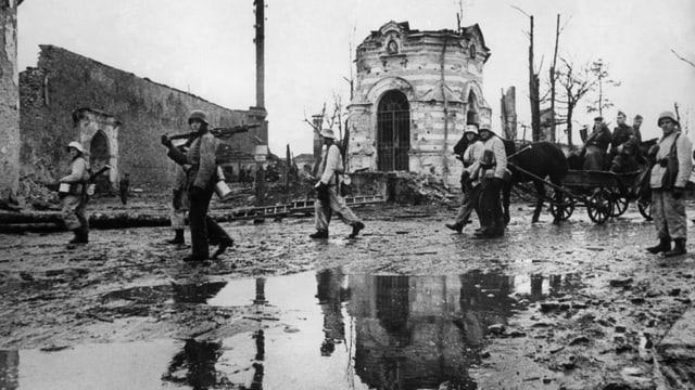 Eine verregnete, schlammige Strasse. Im Hintergrund ein zerbomtes Gebäude. Vereinzelte Soldaten und en Pferdewagen gehen der Strasse entlang.