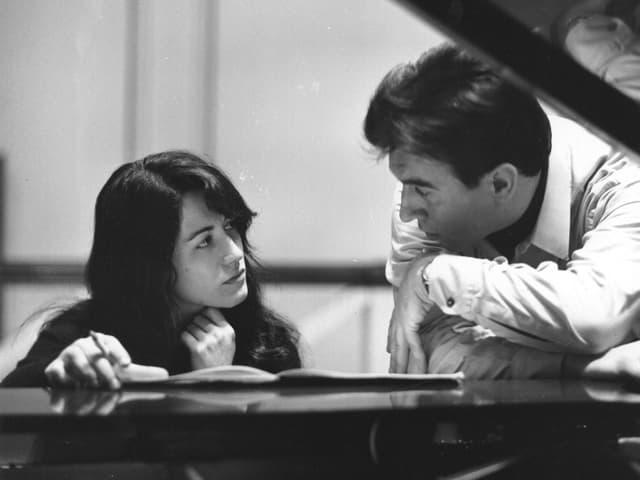 Ein Mann und eine Frau sitzen am Klavier und diskutieren miteinander.