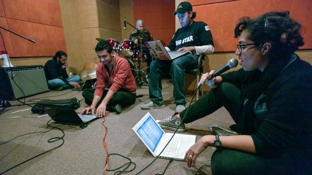 Musiker sitzen am Boden, vor ihnen Laptops, Verstärker, in der Ecke ein Schlagzeuger.