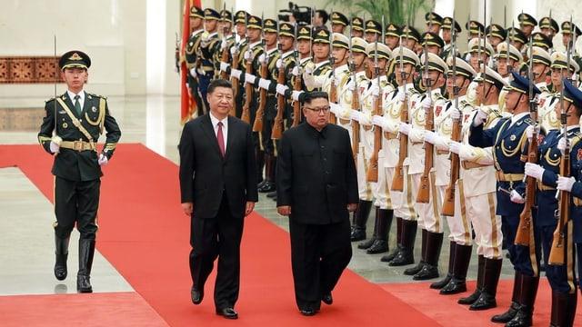 Xi und Kim eine Ehrengarde abschreitend.