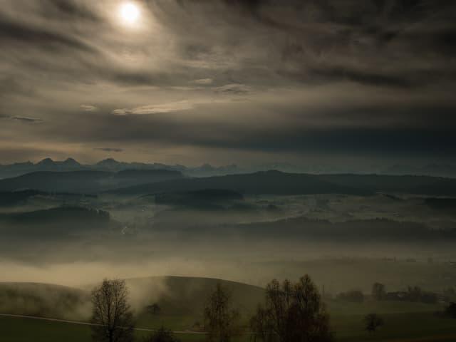 Ein Grau - Verlauf am Winterhimmel, das Sonnenlicht dringt nur noch schwach hindurch.