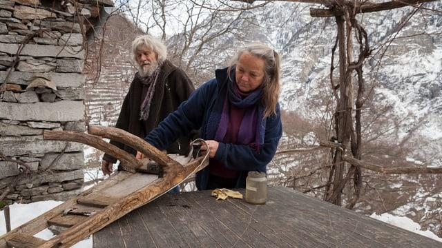 Ulrico und seine Frau Sanna basteln an einem Gegenstand aus Holz herum.