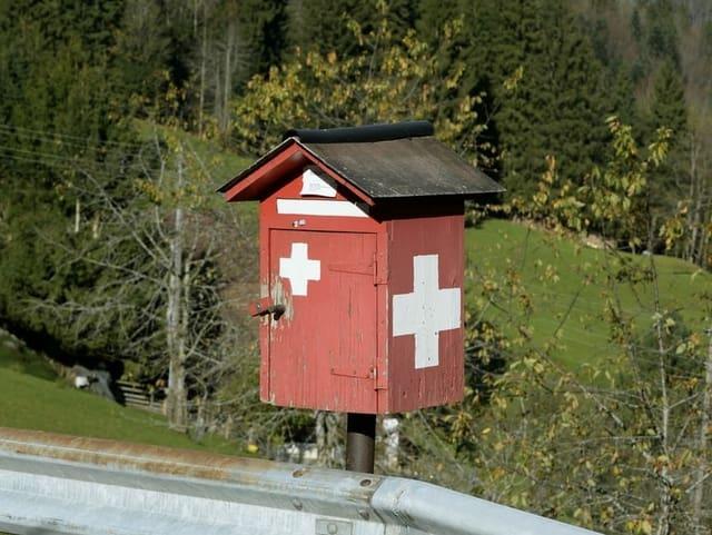 Hölzerner Briefkasten mit Schweizer Kreuz.