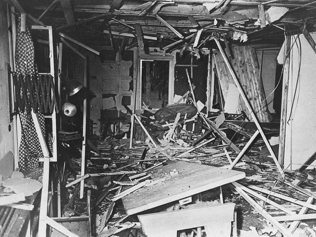 Historisches Schwarzweiss-Bild: Von einer Bombe zerstörter Raum mit kaputtem Tisch und zahlrechen herumliegenden Holzstücken