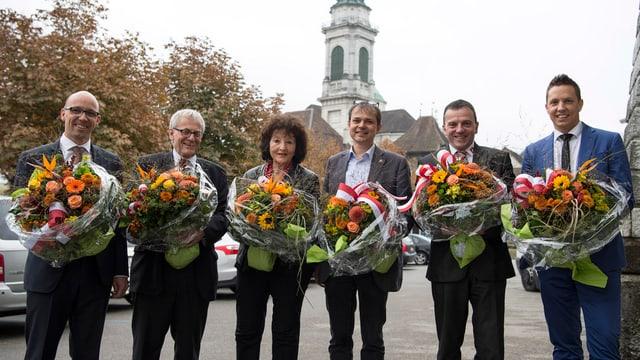 Sechs Leute stehen vor Kirchturm