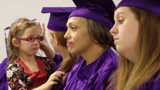 rauen in violetten Abschlussroben, eine hat ein weinendes Kind auf dem Arm.