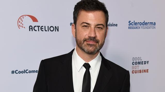 Jimmy Kimmel posiert im Anzug vor einer weissen Fotowand