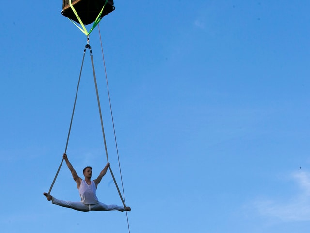 Mann hängt an Heissluftballon macht Akrobatik