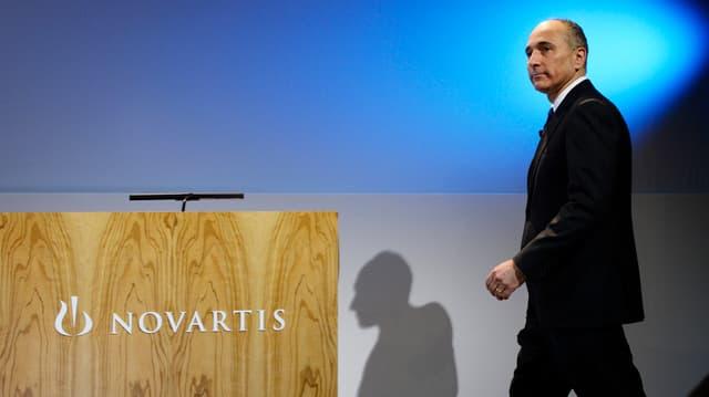 """Joe Jimenez geht auf ein Rednerpult zu, welches mit """"Novartis"""" angeschrieben ist."""