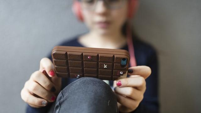 Eine Jugendliche schaut in ein Mobiltelefon.