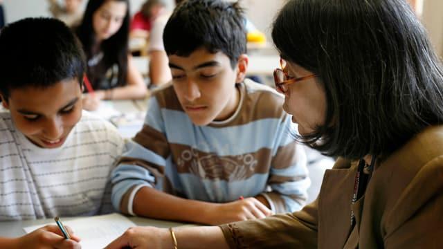 Eine Lehrerin erklärt zwei Buben eine Aufgabe