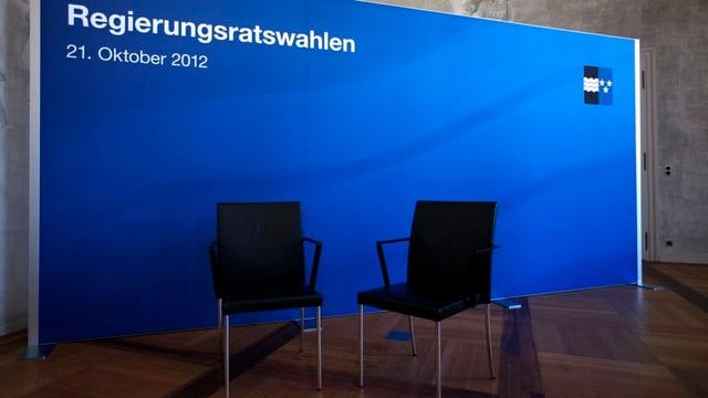 """Zwei leere Stühle vor einer Leinwand mit dem Aufdruck """"Regierungsratswahlen"""" und dem Aargauer Wappen (Symbolbild)."""