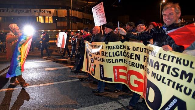 Demonstranten mit einem Banner auf einer Strasse gehend