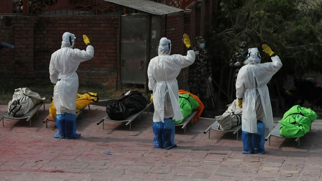 Männer in Schutzanzügen salutieren vor den aufgebahrten, in bunte Tücher gewickelte Leichen.