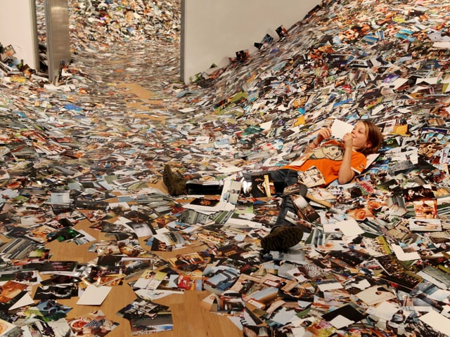 Ein Kind liegt in einem monumentalen Haufen Bilder.