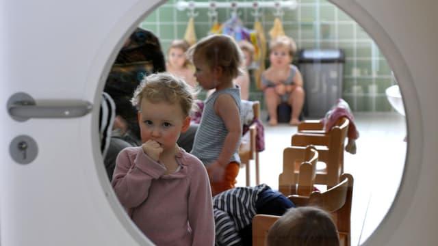 Blick durch Türfenster in eine Krippe, wo Kinder spielen.