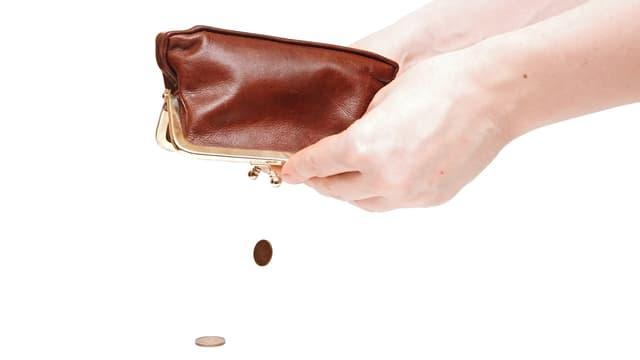 Zwei Händ schütteln ein Portemonnaie aus.