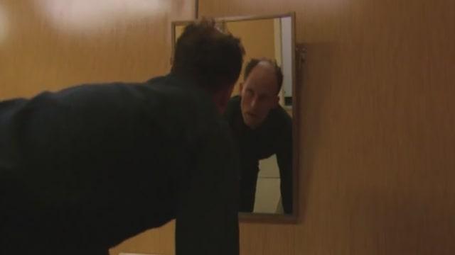 Ein Mann schaut sich im Spiegel an.