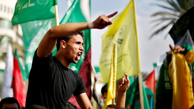 Junger Mann mit erhobenen Zeigefinger auf einer Demonstration.