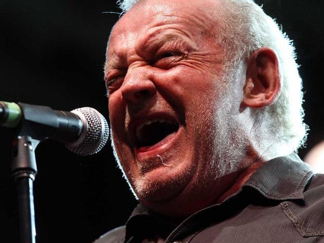 Joe Cocker mit zusammengekniffenen Augen am Mikrofon.