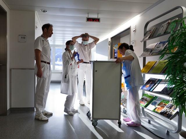 Eine Ärztin und zwei Ärzte stehen vor einem Patientenzimmer im Spital und beraten sich.