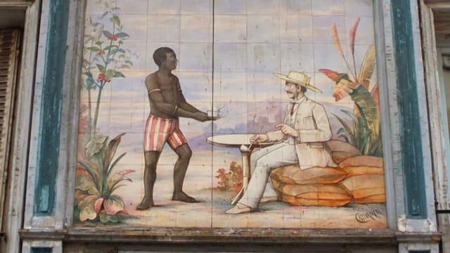 Aussenansicht des «Au Planteur». Auf die Fassade ist ein Schwarzer gemalt, der einem Kolonialherrn dient.