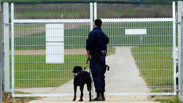 Ein Wachmann mit Hund steht vor einem Zaun bei Agroscope in Reckenholz-Tänikon.