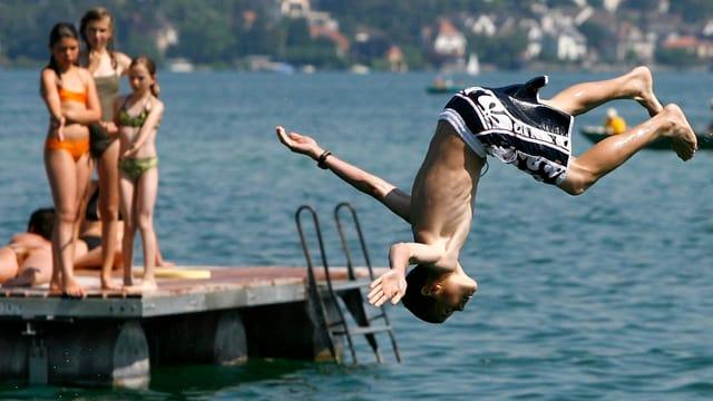 Ein Junge springt in den See, per Salto, auf einem Schwimmfloss schauen Mädchen ihm zu.