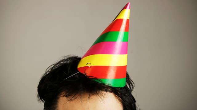 Oberer Teil eines Kopfs mit Partyhütchen