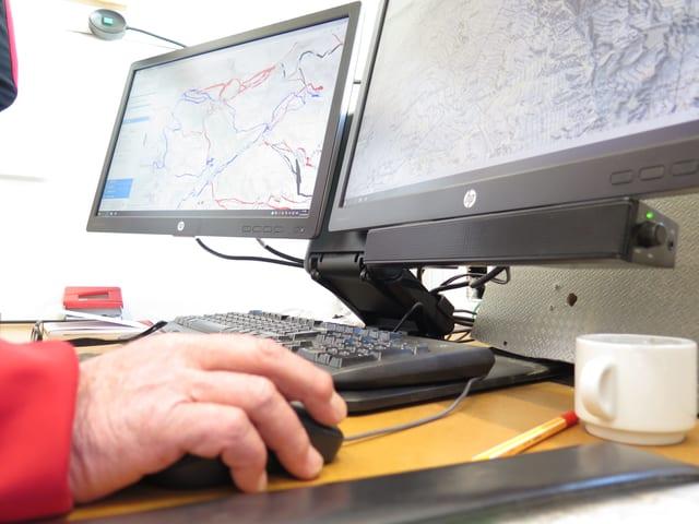Zwei Computerbildschirme. Eine Hand bedient eine Computermaus.