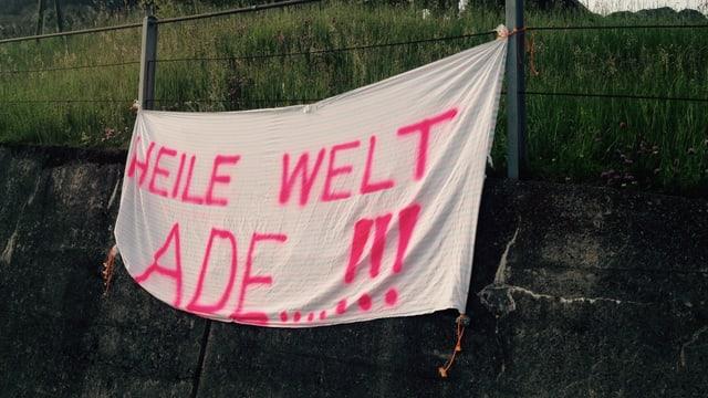 """Leintuch mit Aufschrift """"Heile Welt ade""""."""
