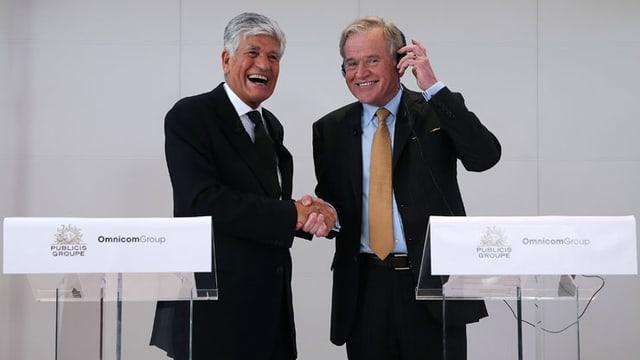 Die Chefs der beiden Werbeunternehmen Maurice Levy und John Wren geben sich lachend die Hand.
