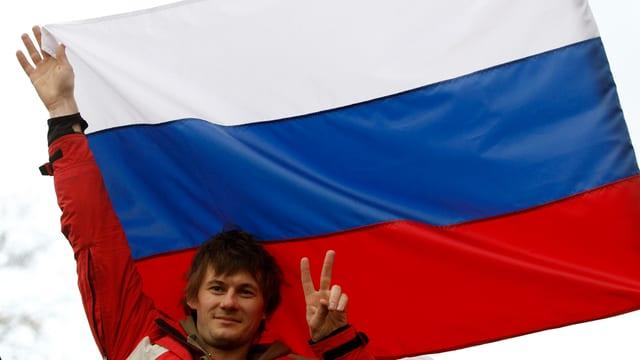 Ein Mann macht mit zwei Fingern ein V-Zeichen vor einer grossen Russland-Fahne.