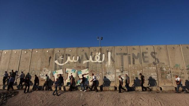Männer laufen einer Mauer entlang