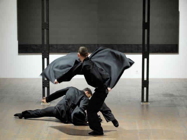 Zwei dunkel gekleidete Männer bewegen sich dynamisch gegeneinander.