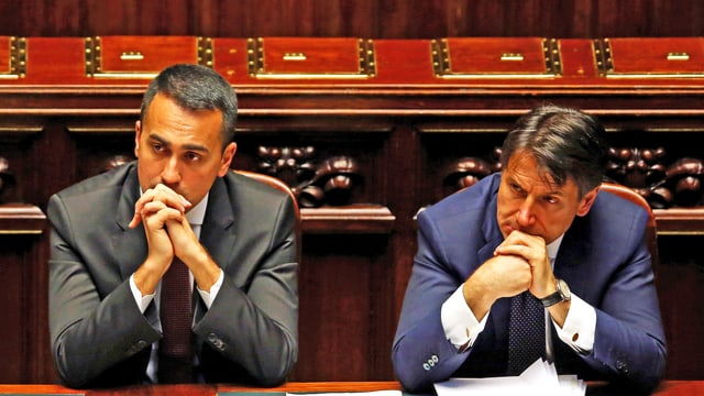 Di Maio und Conte sitzen im Parlament, das Kinn in die Hände gestützt und hören zu.
